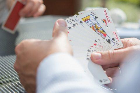 Dua pria memegang kartu poker di tangan mereka.  Dengan seorang pria, kartu terlihat.